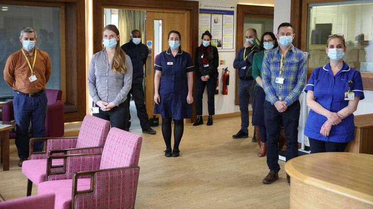 Healthcare workers and staff members observe a minute of silence during the day of reflection to mark the anniversary of Britain's first coronavirus disease (COVID-19) lockdown, at the Marie Curie Hospice in Hampstead, in London, Britain, March 23, 2021. REUTERS/Tom Nicholson