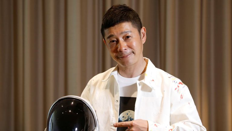 Mr Maezawa poses with a space suit helmet during an interview
