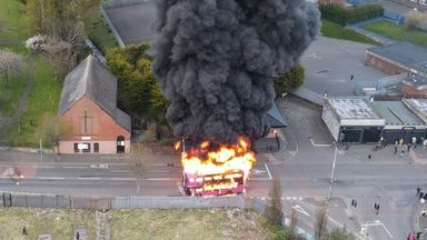 Smoke billows over a neighbourhood in Belfast after a bus was set on fire on another evening of violence.
