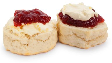 Studio shot of homemade scones, clotted cream and strawberry jam. It is traditional in the county of Cornwall, UK to have the cream on top of the jam. In Devon, UK, the jam is on top.