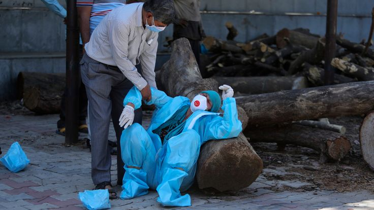 A relative of a person who died of COVID-19 breaks down during cremation in Jammu, India. Pic: AP