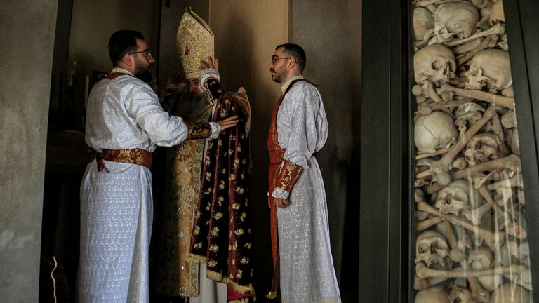 A Lebanese-Armenian bishop adjusts his garment inside the cemetery of Armenians. Pic: Associated Press
