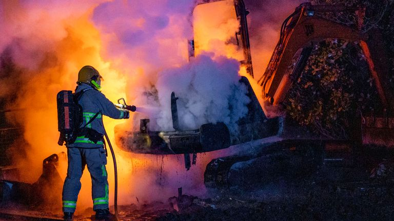 A firefighter putting out a fire on a JCB digger set alight near Loyalist Nelson Drive Estate in Co. Londonderry