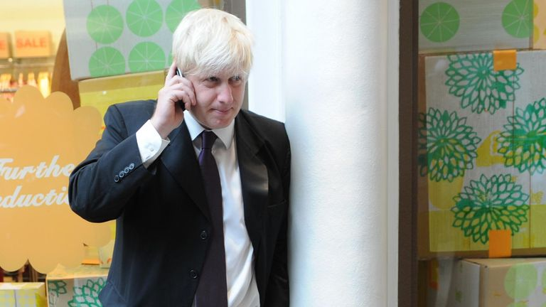 London Mayor Boris Johnson takes a phone call on Kensington High Street in west London where he began a period of consultation on the future of the Congestion Charge western extension