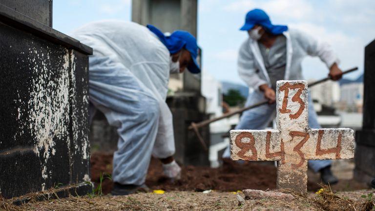 کارگران گورستان با پوشیدن تجهیزات محافظتی ، خاک بیل را روی تابوت حاوی بقایای ماریانا دی عیسی 77 ساله ، که در اثر عوارض مربوط به COVID-19 درگذشت ، در پایان مراسم دفن در قبرستان ایناهوما در ریودوژانیرو ، برزیل ، چهارشنبه ، 28 آوریل 2021. عکس: AP