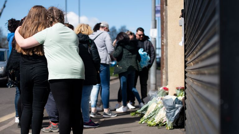 People embrace as flowers and tributes are left at the scene