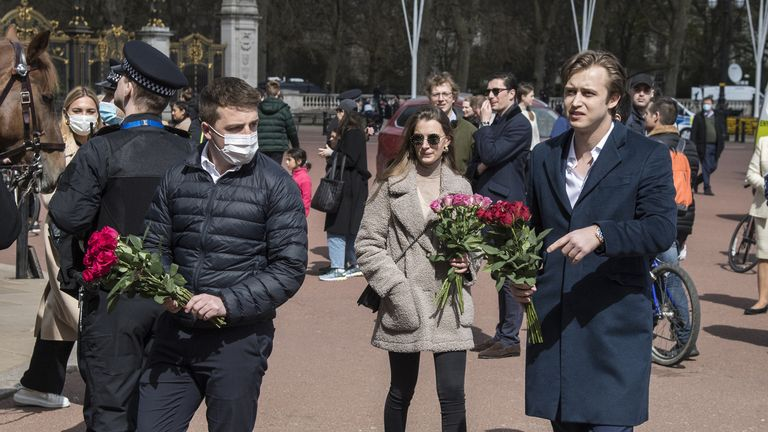 Member of the public carry flowers to leave at the gates of Buckingham Palace, London, following the announcement of the death of the Duke of Edinburgh at the age of 99. Picture date: Friday April 9, 2021.
