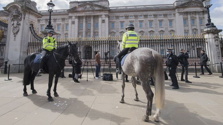 Metropolitan Police officers on horseback observe as members of the media gather outside Buckingham Palace, London, where the Union Flag is flying at half mast following the announcement of the death of the Duke of Edinburgh at the age of 99. Picture date: Friday April 9, 2021.
