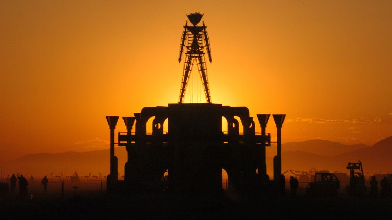 FILE - In this Sept. 2, 2006 file photo, The Man, a stick figured symbol of the Burning Man art festival, is silhouetted against a morning sunrise in Nevada's Black Rock Desert.