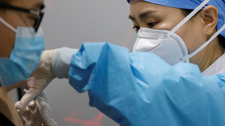 A medical worker prepares to administer a COVID-19 vaccine to a man at a vaccination site in Beijing, China