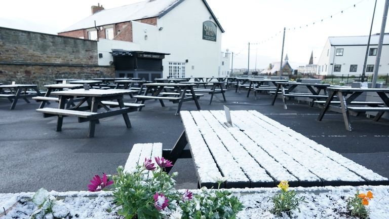 A light dusting of snow covers the outdoor seating area at the Queens Head in Cullercoats, on the North East coast, as the pub prepares to reopen its outdoor area