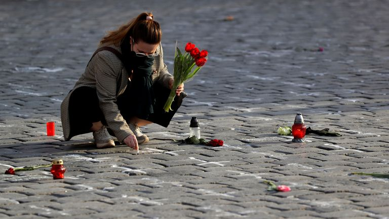 A woman writes a name of her deceased loved one at the Old Town Square in Prague, Czech Republic (file pic)