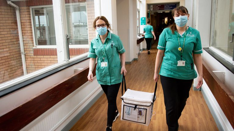 Pharmacists transport a cooler containing the Moderna vaccine, at the West Wales General Hospital in Carmarthen, the third vaccine to be approved for use in the UK, which is to be given to patients in Wales from Wednesday. Picture date: Wednesday April 7, 2021.