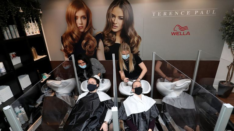 Louise Boothby (L) and Chloe Travis have their hair washed at a salon in Knutsford, Cheshire