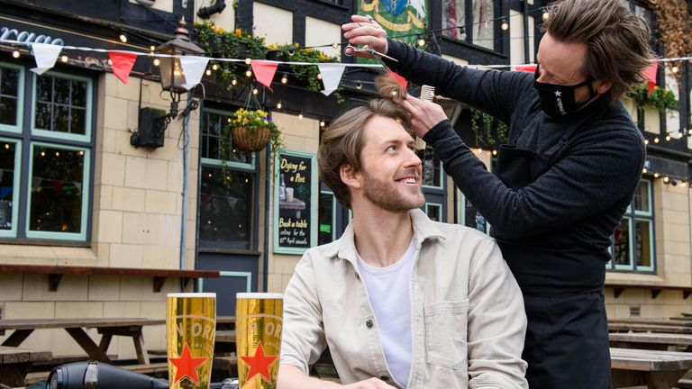 Joe Foyster managed to combine two of things people have been missing at a pop-up hairdressing station at The Gregorian pub in Bermondsey, London. Barber Michael Douglas makes sure there's a good head on it