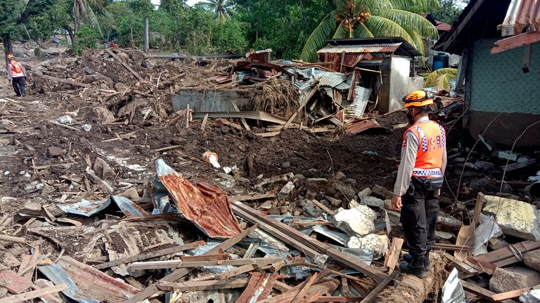 A police officer stands amid the rubble of buildings during a search for victims at a flood-affected village in Ile Ape on Lembata Island, East Nusa Tenggara province, Indonesia, Thursday, April 8, 2021. Multiple disasters triggered by Tropical Cyclone Seroja in eastern Indonesia and neighboring East Timor have left a number of people dead or missing. (AP Photo/Ricko Wawo)