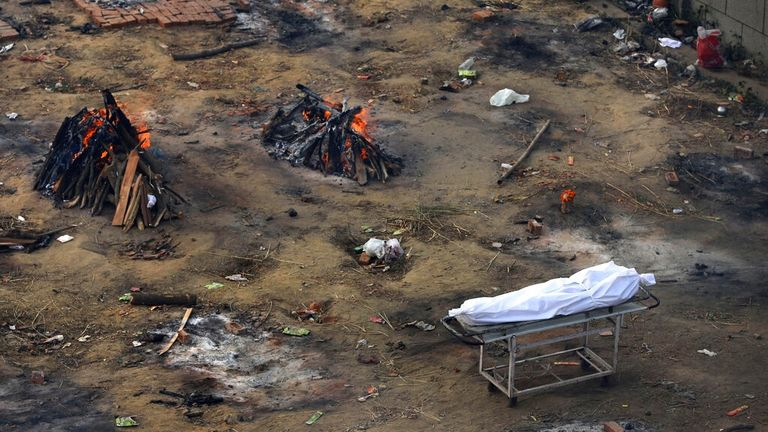 A dead body is due to be cremated as multiple funeral pyres of COVID victims burn at a makeshift crematorium in New Delhi. Pic: AP