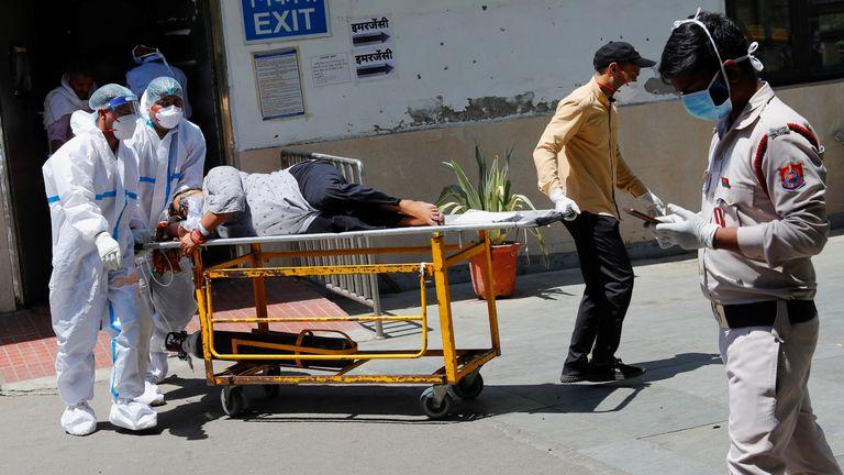 عاملون صحيون ينقلون مريضًا بفيروس كورونا في دلهي