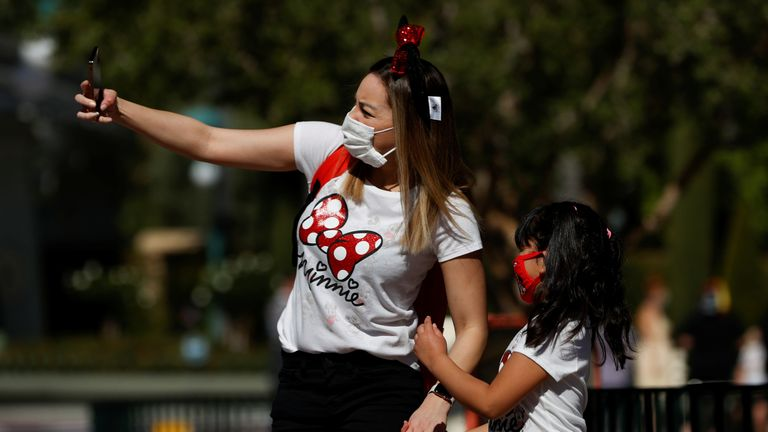 People take a selfie outside Disneyland Park on its reopening day amidst the coronavirus disease (COVID-19) outbreak, in Anaheim, California, U.S., April 30, 2021. REUTERS/Mario Anzuoni