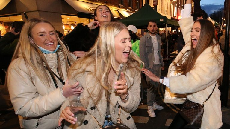 People celebrate being out for the evening in Old Compton Street, Soho, central London, where streets have been closed to traffic to create outdoor seating areas for the reopening bars and restaurants 12/4/2021