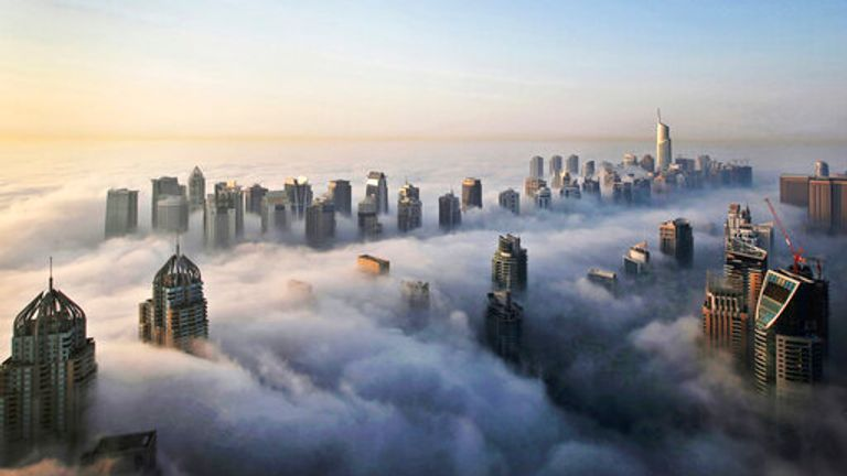 FILE - In Oct. 5, 2015 file photo, a thick blanket of early morning fog partially shrouds the skyscrapers of the Marina and Jumeirah Lake Towers districts of Dubai, United Arab Emirates. Police in Dubai arrested a group of people on charges of public debauchery, authorities said Saturday, April 3, 2021, over a widely shared video that showed naked women posing on a balcony in the Marina. (AP Photo/Kamran Jebreili, File)