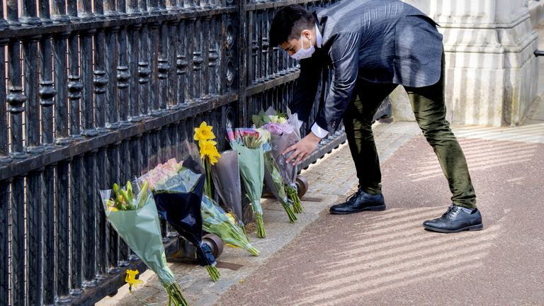 A member of the public leaves flowers outside Buckingham Palace, London, following the announcement of the death of the Duke of Edinburgh at the age of 99. Picture date: Friday April 9, 2021.