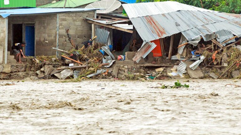 A man inspects buildings damaged by a flood in Dili, East Timor, Monday, April 5, 2021. Multiple disasters caused by torrential rains in eastern Indonesia and neighboring East Timor have left dozens of people dead and missing and displaced thousands. (AP Photo/Kandhi Barnez)