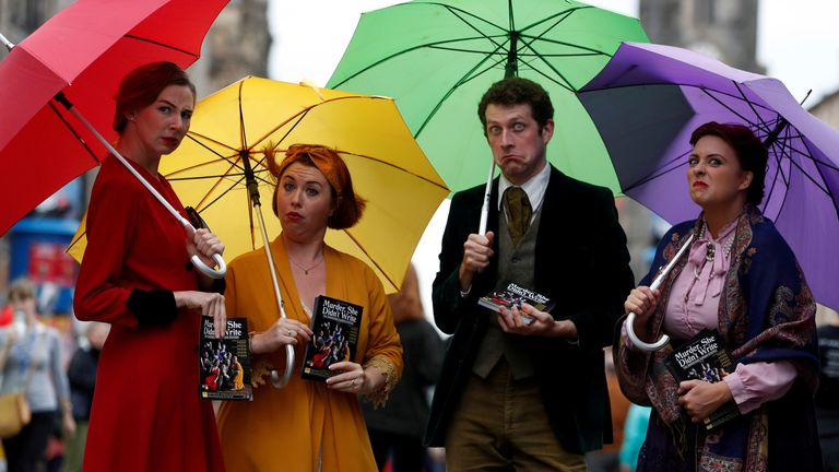 Performers hand out flyers on the The Royal Mile trying to attract people to their show, in Edinburgh, Scotland, in August 2019