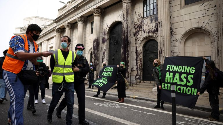 A police officer detains an activist from the Extinction Rebellion, a global environmental movement, during a protest outside the Bank of England building, in London, Britain, April 1, 2021. REUTERS/Henry Nicholls