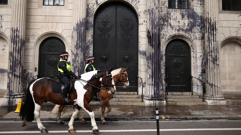 Police officers on horseback pass by the Bank of England building which has been sprayed with black liquid during a protest by Extinction Rebellion activists, a global environmental movement, in London, Britain, April 1, 2021. REUTERS/Henry Nicholls
