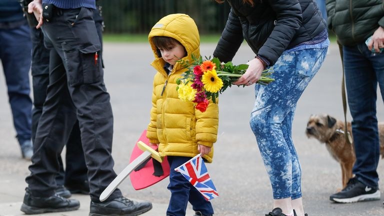 A child and his mother arrive to lay down flowers outside Windsor Castle