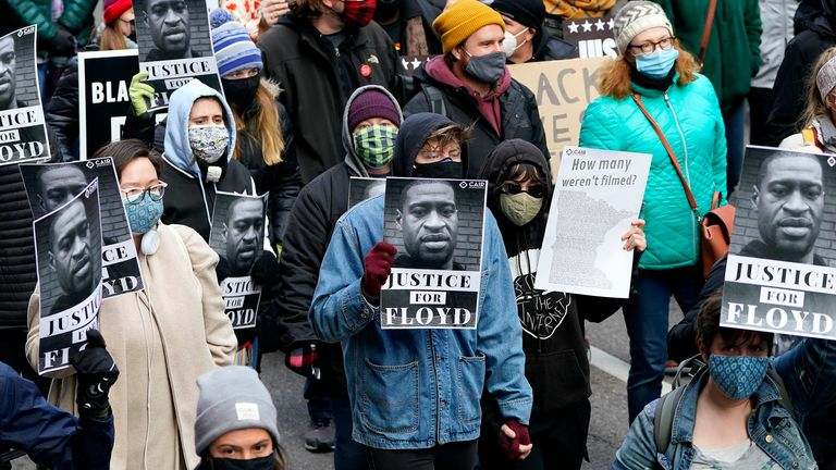 People hold signs as they march near the Hennepin County Government Center during a rally in Minneapolis on Monday, April 19, 2021, after the murder trial against former Minneapolis police officer Derek Chauvin advanced to jury deliberations. (AP Photo/Julio Cortez)
