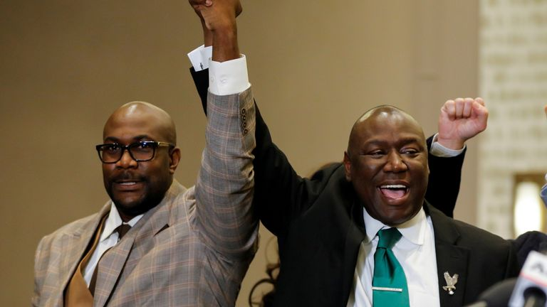 Philonise Floyd (left) raises his hand in celebration with family lawyer Ben Crump