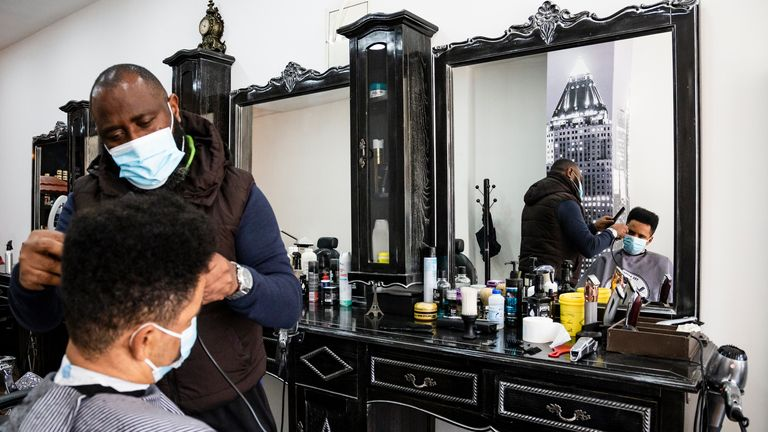 A hairdresser wearing a face mask cuts a costumers hair short at a barbershop amid coronavirus crisis. On March 11, the deconfination program was announced and will be gradually, divided into 4 parts, in a period that goes until Easter, and may have setbacks. Starting this Monday with the opening of kindergartens, 1st cycle, hairdressers, manicurists, real estate, bookstores and wicket coffee service. (Photo by Rita Franca / SOPA Images/Sipa USA)