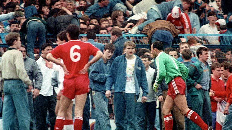 Liverpool goalkeeper Bruce Grobbelaar (r) and Alan Hansen (6) can only watch as the tragic events unfold around them. 96 people in total lost their lives after a crush occurred during the match.