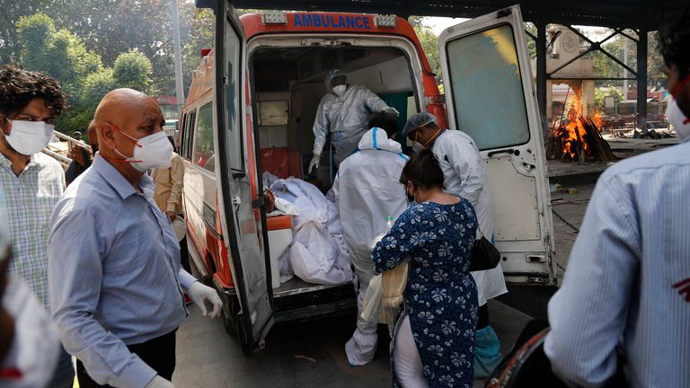 Health workers prepare to take out from an ambulance bodies of six people who died of COVID-19 . Pic: AP