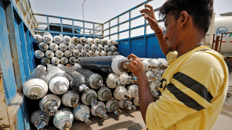 A worker loads empty oxygen cylinders onto a van in Ahmedabad