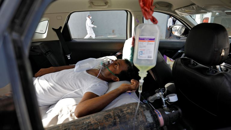 A patient in a car waits to enter a Ahmedabad hospital for COVID treatment
