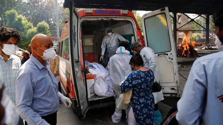Workers prepare to remove the bodies of six COVID victims in New Delhi on Monday