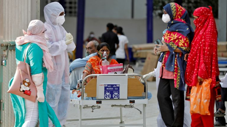 Patients sit on a bed, waiting to be moved to a hospital in Ahmedabad, India