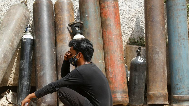A man waits outside a factory to get his oxygen cylinder refilled amid the continuing surge in coronavirus infections in India