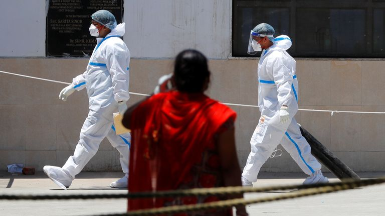 A health worker wearing personal protective equipment (PPE) carries an oxygen cylinder into the casualty ward at Guru Teg Bahadur Hospital, in New Delhi, India, April 24, 2021. REUTERS/Adnan Abidi