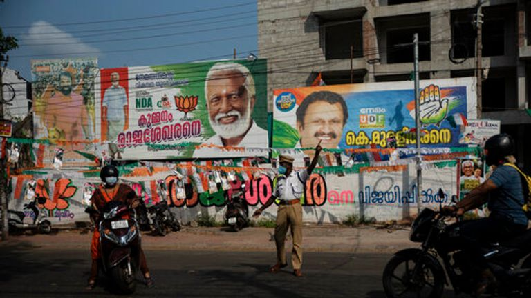 A policeman directs traffic standing before a display of election campaign posters of various candidates at Nemom constituency in Thiruvanathapuram, Kerala state, India, Saturday, April 3, 2021. The southern state goes to polls on April 6. (AP Photo/R S Iyer)