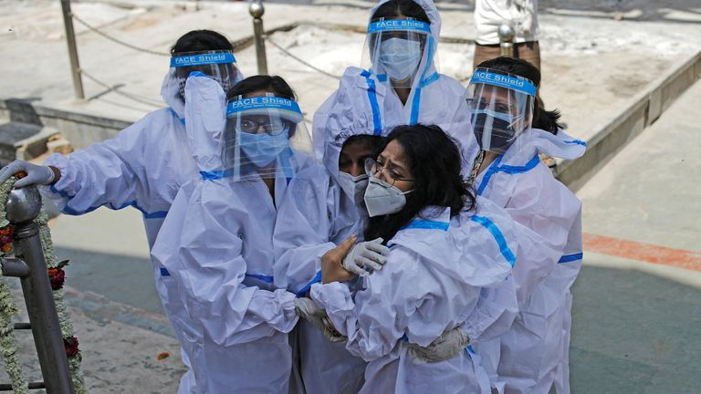 Relatives wearing personal protective equipment (PPE) mourn a man, who died from the coronavirus disease (COVID-19), at a crematorium in New Delhi, India April 21, 2021. REUTERS/Adnan Abidi