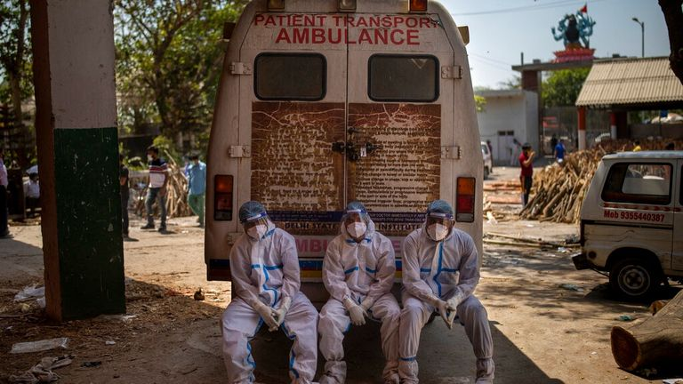 Exhausted workers, who bring dead bodies for cremation, sit on the rear step of an ambulance inside a crematorium, in New Delhi, India