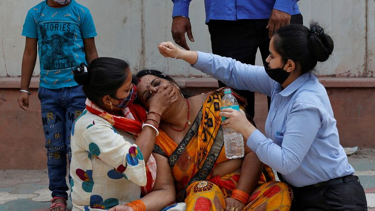 A mourner is consoled after her husband died of COVID-19 in New Delhi. India recorded 200,000 cases on 16 April
