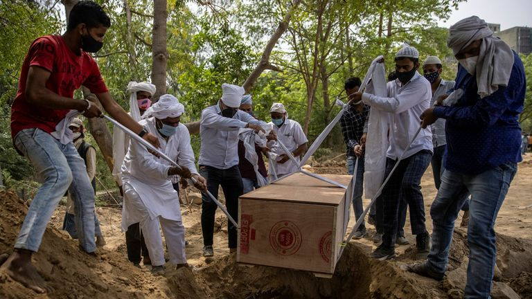 People bury the body of a man, who died from coronavirus disease at a graveyard in New Delhi