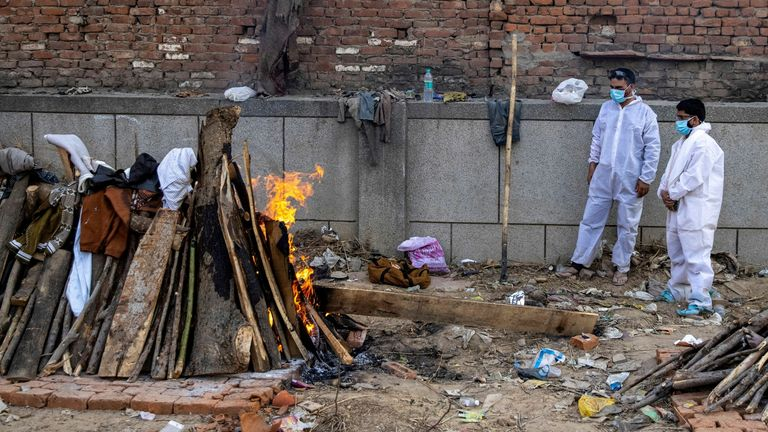 Relatives stand next to the burning funeral pyre at a crematorium ground in New Delhi