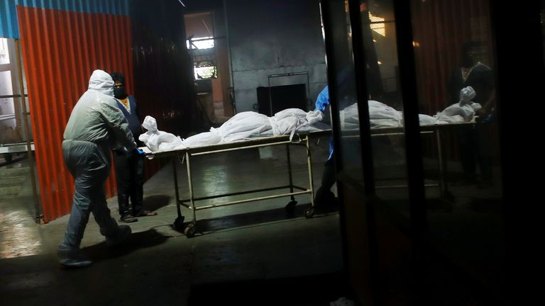 The body of someone who died with coronavirus being pushed into a crematorium in Delhi
