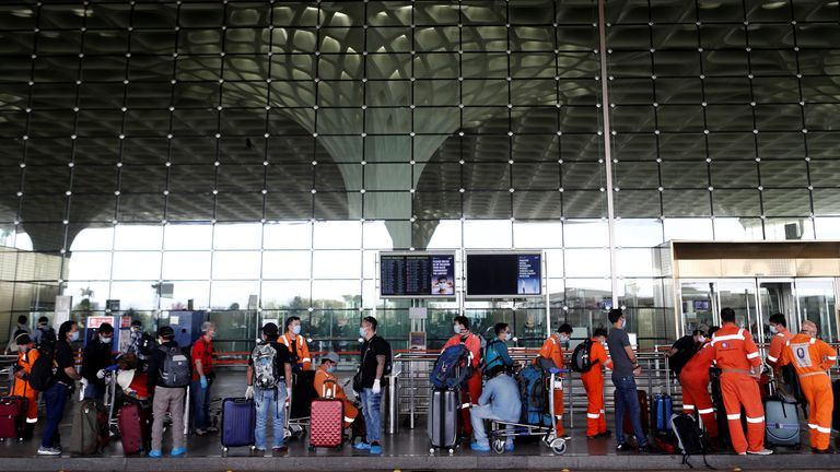 Passengers wearing protective face masks wait in a queue to enter Chhatrapati Shivaji International Airport, after the government allowed domestic flight services to resume, during an extended nationwide lockdown to slow the spread of the coronavirus disease (COVID-19), in Mumbai, India, May 25, 2020. REUTERS/Francis Mascarenhas